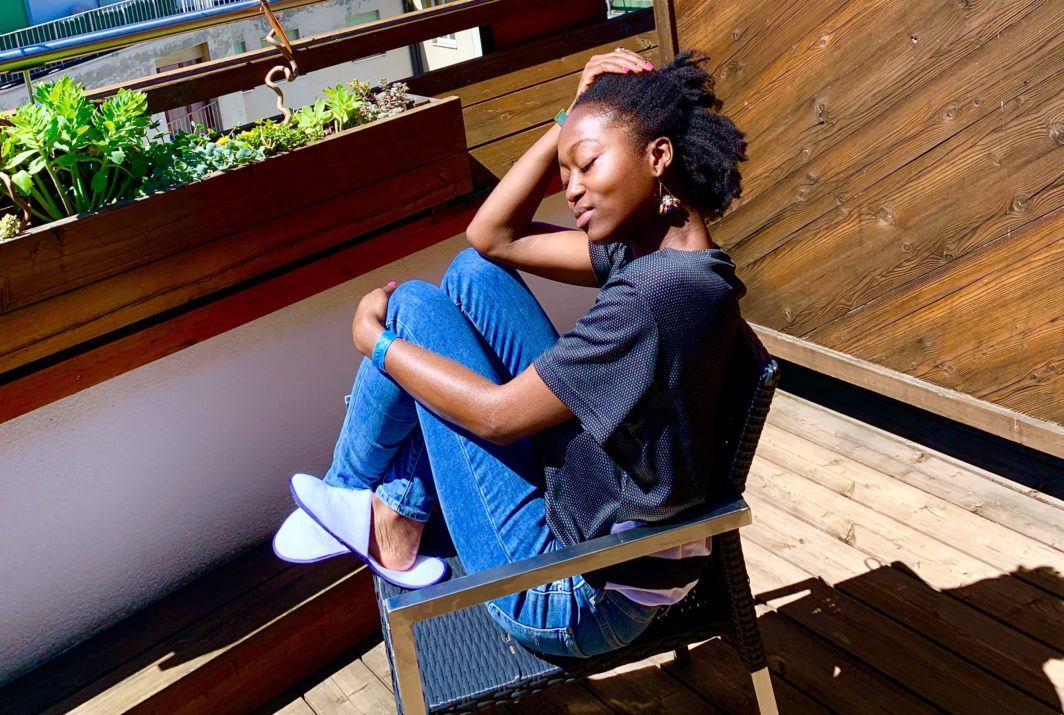 blogging status natural hair black swiss influencer on a wooden balcony in geneva