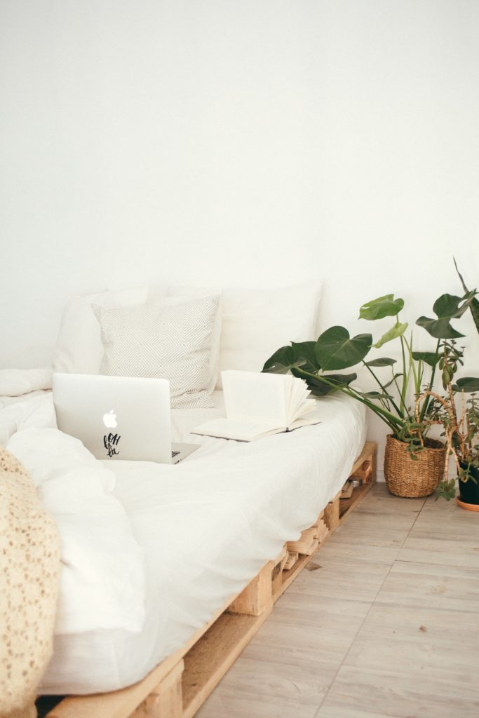 book and computer on bed made of wood pallet with white sheets in a room full of green plants